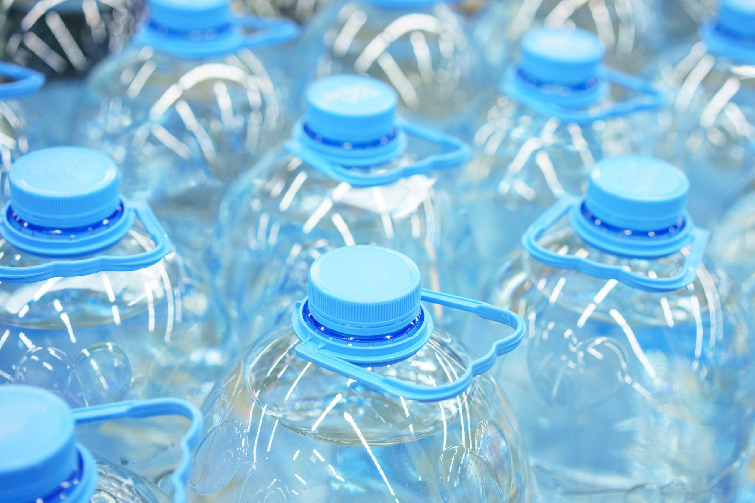 Five-liter plastic drinking water bottles close-up, soft focus